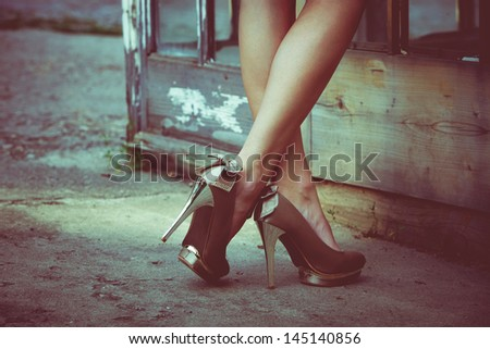 woman  legs in high heel shoes against old door with glass  outdoor shot retro colors - stock photo