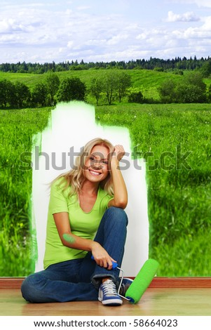 woman paint green field on the wall - stock photo