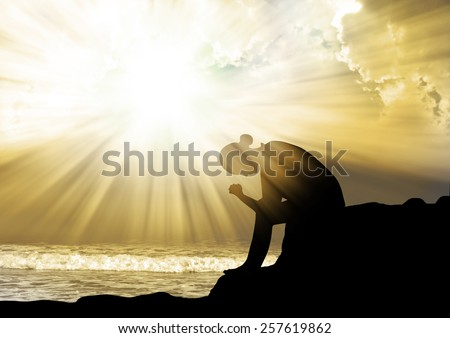 Woman praying to god  at sunset - stock photo