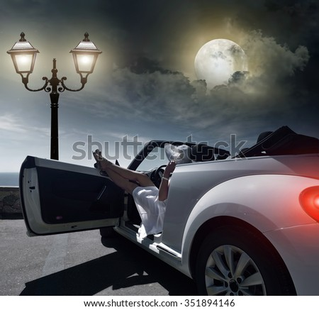Woman resting at night on the waterfront in the car. - stock photo