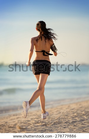 Woman runner on beach, back view - stock photo