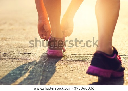 woman runner tying shoelaces in the morning