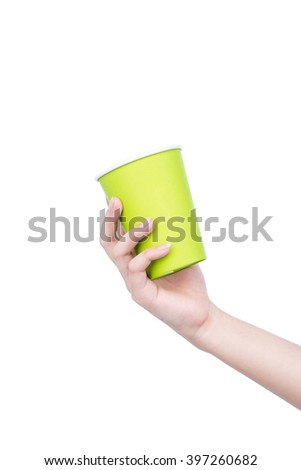 woman's hand holding green empty paper coffee cup isolated on a white background in the studio, advertising coffee