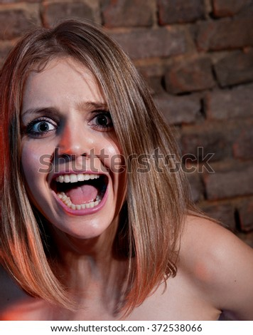 Woman screaming in terror on the brick wall background.
