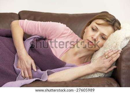 Woman Unwell And Lying On Sofa - stock photo