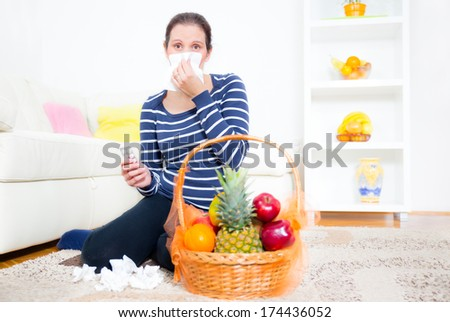 woman with a cold blowing nose and holding pills - stock photo