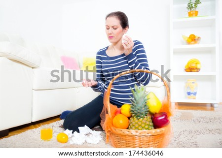 woman with a cold holding pills - stock photo