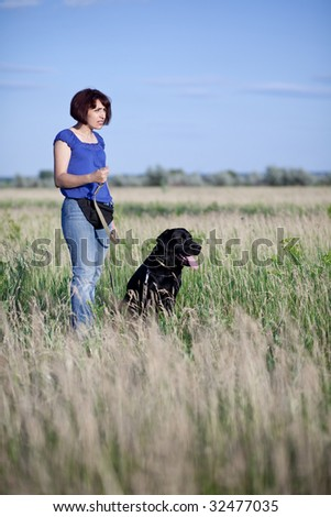 woman with  dog in field - stock photo