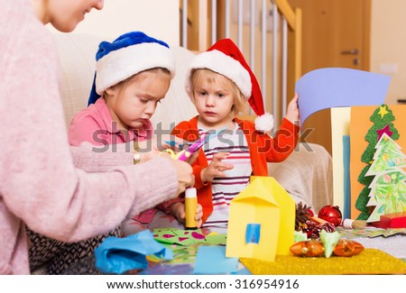 woman with two girls preparing for Christmas at home