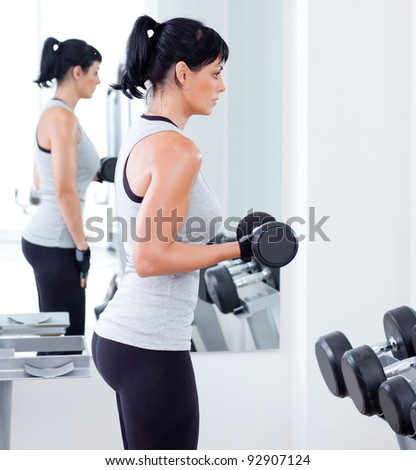 woman with weight training equipment on sport gym club - stock photo