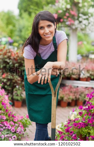 Woman working in garden center smiling while leaning on spade - stock photo