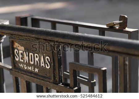 """Women"" sign in spanish language. Black iron fence."