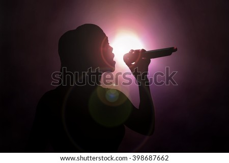 Women singing under spotlight - stock photo