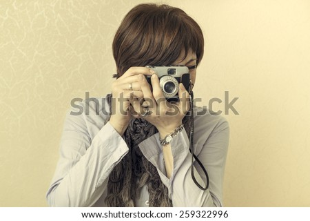 women taking photographs with vintage retro camera, sepia - stock photo