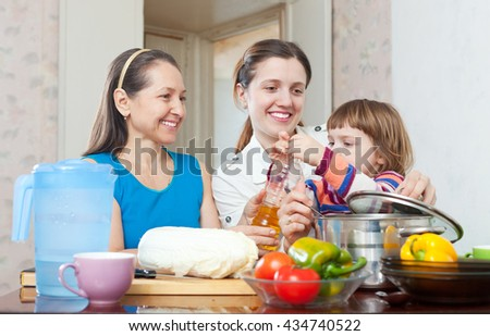 women with child cook vegetables in kitchen at home