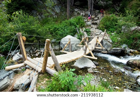 Wooden bridge over a river in Retezat Mountains,Romania. - stock photo