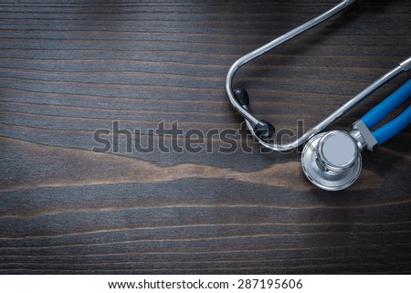 Wooden vintage board with blue medical stethoscope horizontal view medicine concept - stock photo