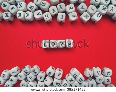 Word Love of small white cubes next to a bunch of other letters on the surface of the composition on a red background