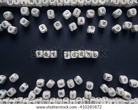 Word Not found of small white cubes next to a bunch of other letters on the surface of the composition on a dark background