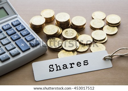 word on tag label with calculator and gold coins, financial concept. - stock photo