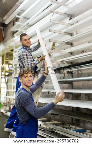 workers working with PVC window profile at stand - stock photo
