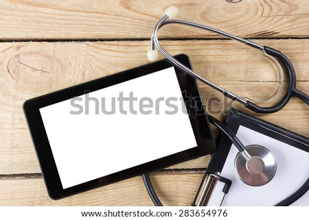 Workplace of a doctor. Tablet, stethoscope, clipboard on wooden desk background. Top view - stock photo