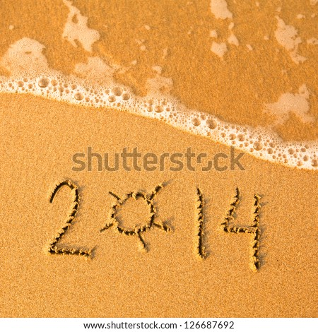 2014 written in sand on beach texture - soft wave of the sea. - stock photo