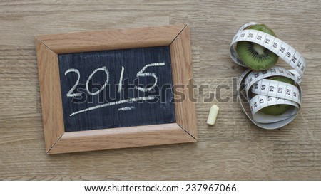 2015 written on a chalkboard next to a kiwi an inches - stock photo