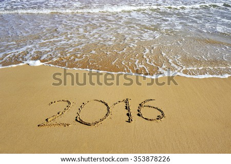 2016 written on sand beach near sea - happy new year concept