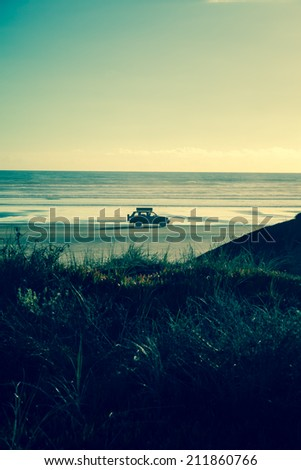4x4 RV van on deserted beach. Driving towards the sun, leaving a nice shadow. Freedom feeling, cruising the beach with a packed car. - stock photo