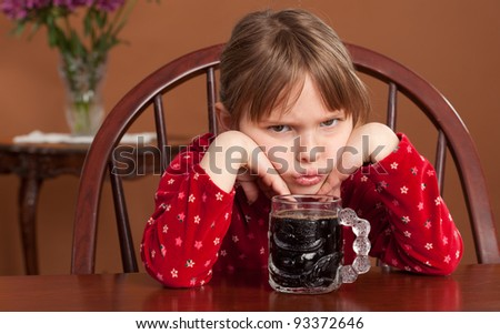 5 y/o child reacts to being served black coffee - stock photo
