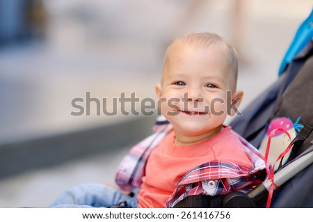 1 year baby sitting in the baby carriage, blonde, gray eyes, a red T-shirt, plaid shirt, blue jeans, a city on the background of green trees. Baby with a pacifier. - stock photo