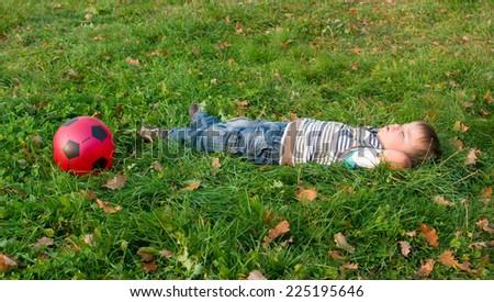 3-year boy sleeping on an autumn grass with a ball - stock photo