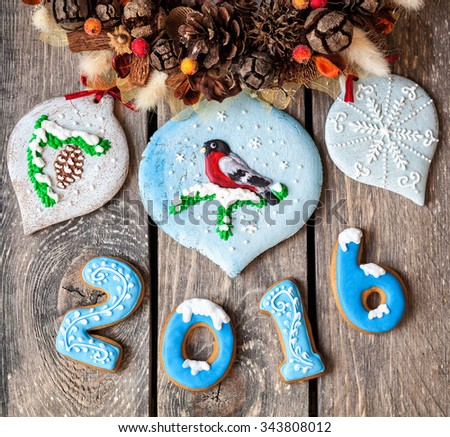 2016 year from gingerbread and bird on Christmas sweet toys near Christmas garland on wooden background