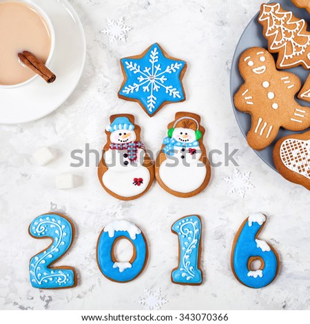 2016 year from gingerbread, snowmen and different gingerbreads near cup of coffee on white background - stock photo