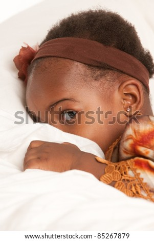 3 year old African American girl in colorful costume playing hide seek - stock photo