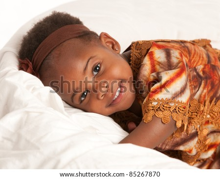 3 year old African American girl in colorful costume sit on bed - stock photo