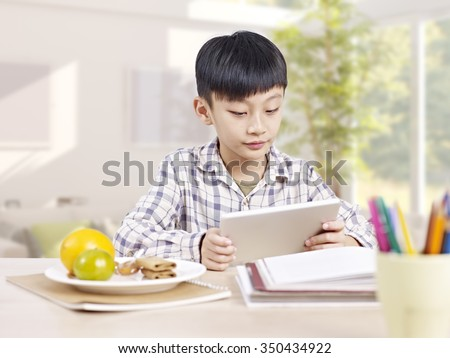 10 year-old asian elementary schoolboy reading using tablet computer. - stock photo