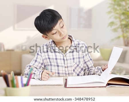 10 year-old asian elementary schoolboy studying and/or doing homework at home. - stock photo