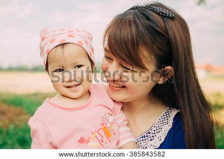 1 year old baby feeling happy and smiles with her mother in the garden