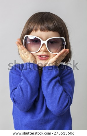 3-year old baby holding huge sunglasses for disguise - stock photo