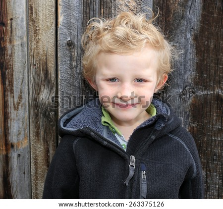 6 year old blond boy with a barn wood background. - stock photo