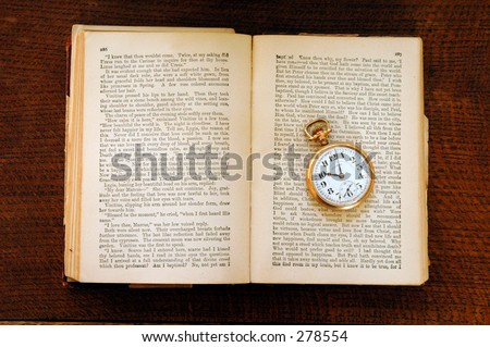 100 year old book with old pocket watch. - stock photo