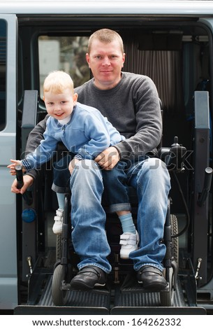 4 year old boy and 35 year old Disabled Men on Wheelchair Lift - stock photo