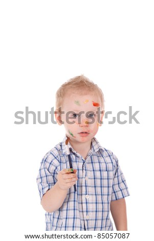 2 year old boy covered in paint. Holding brush, over white - stock photo