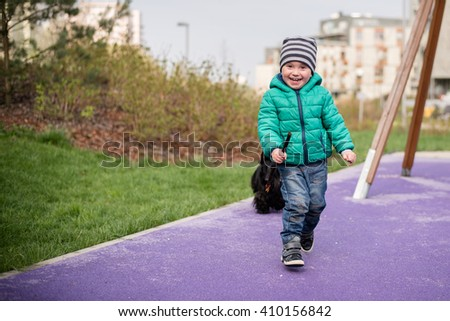 2 year old boy having fun outdoors on playground and running with his dog - stock photo