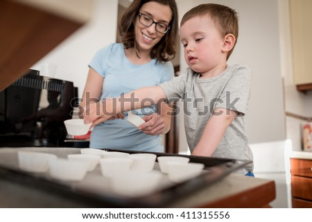 2 year old boy having fun preparing dough for muffins with mother in kitchen at home - stock photo