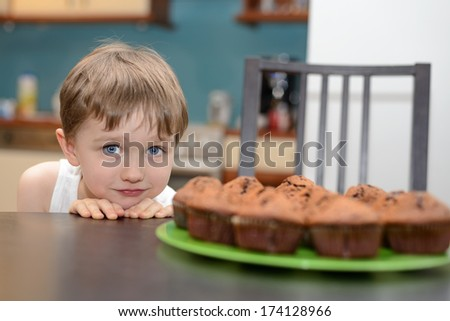 4 year old boy hungrily looking at chocolate cake muffin - stock photo