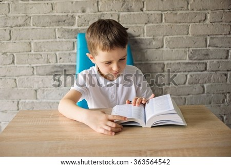 6 year old boy in a white polo shirt reading a book at the table - stock photo