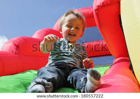 2 year old boy jumping down the slide on an inflatable bouncy castle - stock photo